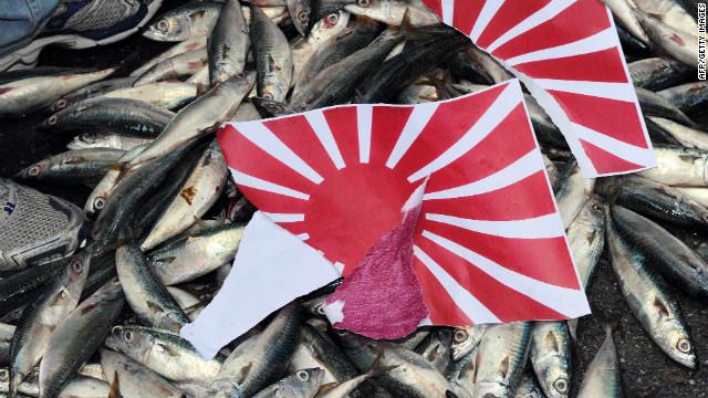 Orang Jepang yang terpecah-pecah & # 39; Matahari Terbit & # 39; Bendera dipasang pada ikan mati selama demonstrasi di Taipei pada 14 September 2010, di atas rantai pulau Senkaku / Diaoyu yang disengketakan.