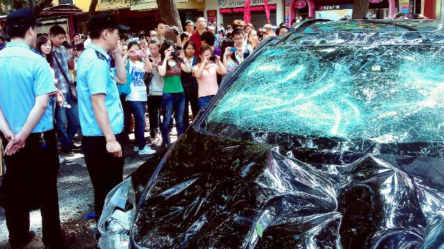 Orang-orang mengambil gambar mobil Jepang yang rusak saat protes menentang nasionalisasi Jepang & # 39; Kepulauan Diaoyu yang disengketakan, juga dikenal sebagai Kepulauan Senkaku di Jepang, di kota Cina Xi, pada 15 September 2012.