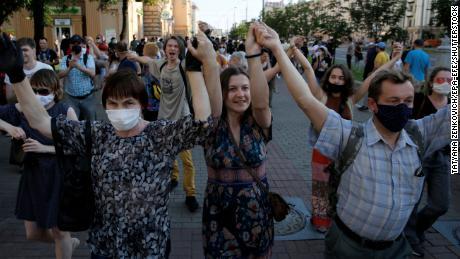 Para pengunjukrasa memegang tangan mereka di udara saat demonstrasi di Minsk pada 19 Juni.