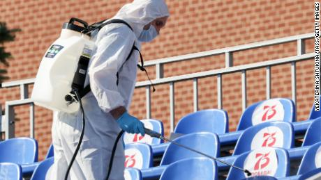 Seorang pekerja sanitasi dengan alat pelindung menyemprotkan disinfektan pada kursi di Lapangan Merah sebelum pawai.