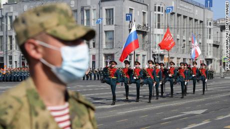 Seorang tentara Rusia mengenakan topeng di Lenin Square selama pawai.