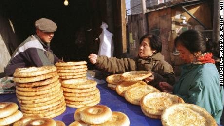 Seorang lelaki Uyghur menjual roti pipih tradisional kepada pembeli wanita di sepanjang Jalan Xinjiang Beijing pada tahun 1999.