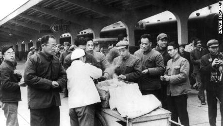 Para pelancong Cina membeli sarapan mereka dari seorang pedagang kaki lima di Stasiun Kereta Chunghow pada tahun 1975. Perdana Menteri Li Keqiang telah menyarankan lebih banyak pedagang kaki lima dapat membantu memperbaiki krisis pekerjaan yang membayangi.