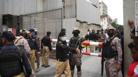 Personel keamanan berkumpul di pintu masuk utama gedung Bursa Efek Pakistan di Karachi pada 29 Juni 2020.
