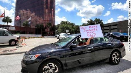 Para guru memprotes di luar markas Sekolah Umum Orange County Florida pada hari Selasa.