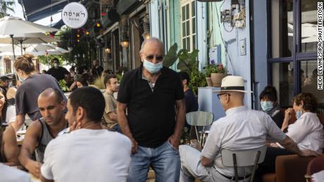 Seorang pria mengenakan topeng pelindung di sebuah restoran ramai di Jaffa, Israel, pada 29 Mei.