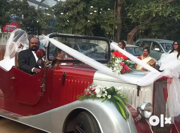 A classic car replica being used as a wedding car