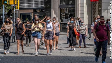 Orang-orang memakai masker di Barcelona, Spanyol, tempat mereka yang tidak melakukannya di ruang publik menghadapi denda 100 euro.