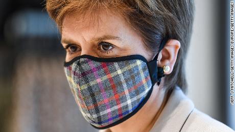 Menteri Pertama Skotlandia Nicola Sturgeon mengenakan masker wajah Tartan saat ia mengunjungi sebuah taman ritel bulan lalu di Edinburgh.