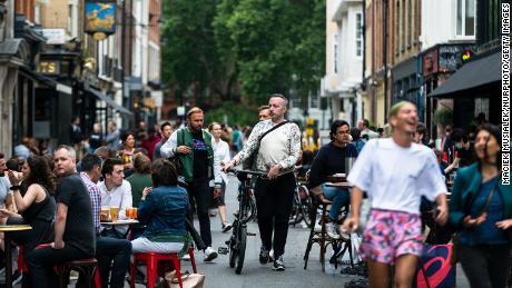 Pelanggan menikmati minuman mereka di Soho, London, awal Juli sebagai pub, restoran, hotel dan penata rambut di Inggris dibuka kembali.