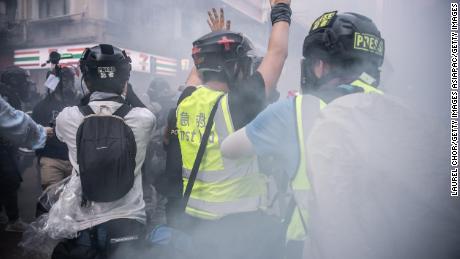 Seorang jurnalis mengangkat tangannya setelah polisi menembakkan gas air mata pada 1 Oktober 2019 di Hong Kong. Tekanan telah meningkat pada wartawan di kota di bawah undang-undang keamanan baru.