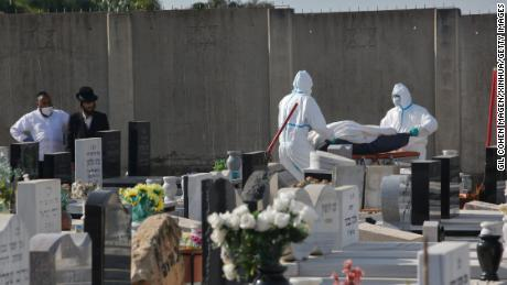 Pekerja pemakaman membawa mayat seorang pasien Covid-19 di sebuah pemakaman di kota Rehovot, Israel tengah pada 21 April.