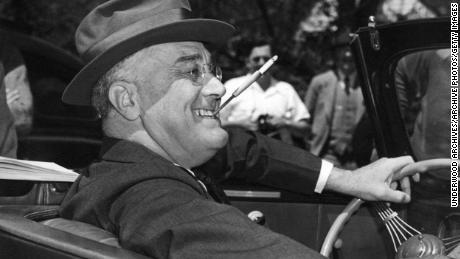 Dengan sebatang rokok di dudukan yang dikepalkan, giginya yang tersenyum, Franklin Delano Roosevelt duduk dengan gembira di atas roda mobil konvertibelnya, Warm Springs, Georgia, 1939. (Foto oleh Underwood Archives / Getty Images)