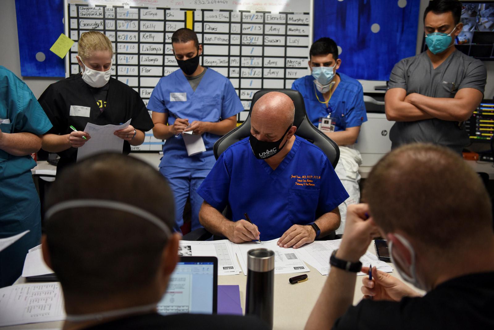 Varon dan timnya memeriksa file pasien selama pertemuan harian.