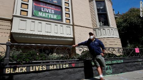 James Juanillo berpose dengan pesan kapur yang ditulis di luar rumahnya di San Francisco, California pada 14 Juni 2020.