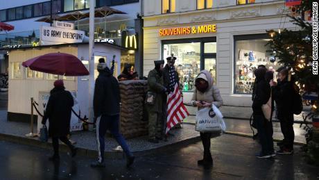 Turis mengambil foto aktor berpakaian tentara di bekas Checkpoint Charlie di Berlin, di mana tank AS dan Soviet saling berhadapan di tahun-tahun awal Perang Dingin.
