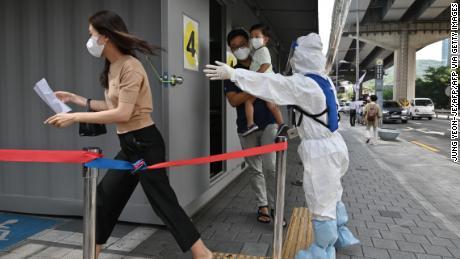 Seorang pejabat kesehatan yang mengenakan alat pelindung memandu pengunjung di stasiun pengujian virus corona Covid-19 di Seoul pada 18 Agustus 2020.