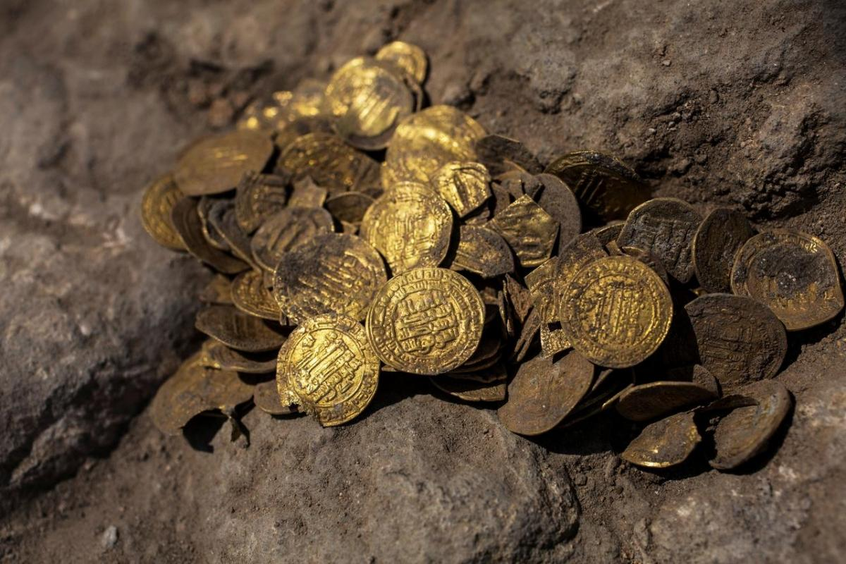 Israeli archaeologist Shahar Krispin shows gold coins, said by the Israel Antiquities Authority to date to the Abbasid dynasty, after its discovery at an archaeological site in Central Israel August 18, 2020. Picture taken August 18, 2020. Heidi Levine/Po