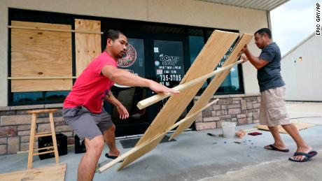 Daoith Porm, kiri, dan Bunsant Khov, kanan, naik ke bisnis mereka dengan Hurricane Laura hanya beberapa jam lagi.