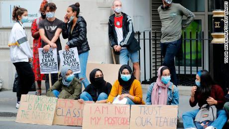 Para siswa memegang plakat saat mereka melakukan protes di luar Departemen Pendidikan di pusat kota London pada 14 Agustus.
