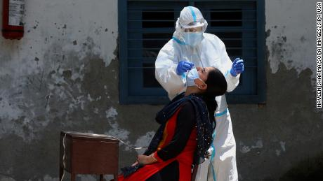 Seorang petugas medis yang mengenakan peralatan pelindung pribadi mengumpulkan sampel swab di India.