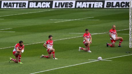 Para pemain St Helens berlutut sebelum pertandingan hari Minggu.