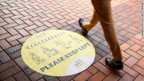 Seorang pejalan kaki berjalan melewati tanda jarak sosial pada 14 Agustus 2020 di Wellington, Selandia Baru.
